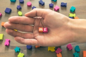 The pure thoughtful hand of a beautiful young girl holds colored cubes with the inscription Me - close-up