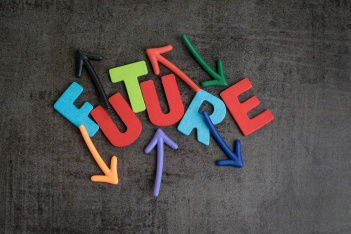 Uncertain future or next unpredictable life goal concept, colorful wooden alphabets combine word FUTURE with random direction arrow on dark black chalkboard wall